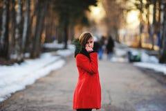 Vorfrühlingsporträt des netten attraktiven ernsten jungen Mädchens mit dem Hitzeschal des dunklen Haares und roter Jacke, die zur Stockfotografie