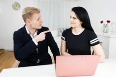 Vorgesetztarbeiten mit Untergebenem, blonder Mann, der mit schwarzer behaarter Frau arbeitet stockfotografie