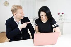 Vorgesetztarbeiten mit Untergebenem Blonder Mannpunktfinger an der schwarzen behaarten Frau stockfotos