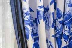 Vorhänge mit blauem Blumenmuster und weißem Tulle auf den Fenstern des Wohnzimmers lizenzfreie stockbilder