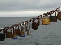 Vorhängeschlösser festgesteckt zur Kette und zur Ostsee Stockfotografie