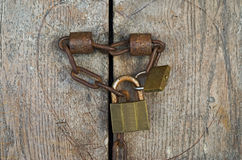Vorhängeschlösser mit Eisenkette von einer alten hölzernen Tür stockfoto