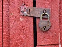 Vorhängeschloß auf alter roter hölzerner Tür stockfotografie