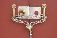 Vorhängeschloß und Kette, die zwei Türen binden Stockfotografie