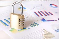 Vorhängeschloß und Finanzdiagramme Stockfotos