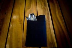 Vork en lepel in donkerblauwe doek, op houten lijstachtergrond stock fotografie