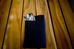 Vork en lepel in donkerblauwe doek, op houten lijstachtergrond royalty-vrije stock fotografie