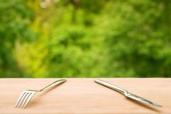 Vork en mes op houten lijst tegen groene gebladerteachtergrond stock foto
