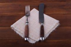Vork en mes op servet op hout Royalty-vrije Stock Afbeeldingen