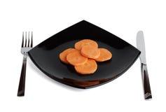 Vork, mes, zwarte plaat en wortel. Drie. Royalty-vrije Stock Fotografie