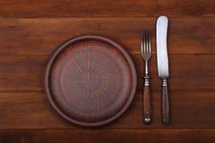 Vork, messen en dinerplaat op een houten achtergrond Stock Afbeelding