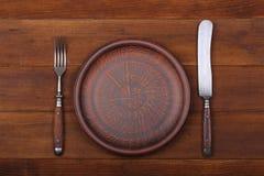 Vork, messen en dinerplaat op een houten achtergrond Royalty-vrije Stock Fotografie