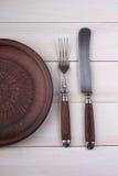Vork, messen en dinerplaat op een licht hout Stock Afbeeldingen