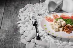 Vork, wijnglas en plaat van ham, okkernoten en kaas op witte rotsen Close-up van gezonde snacks op een houten achtergrond Stock Afbeeldingen