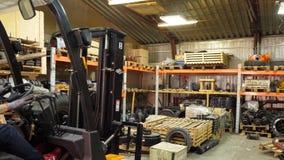 Vorkheftruckbestuurder die in beschermende vest drijfvorkheftruck bij pakhuis van vracht bedrijf door:sturen Mens op de vorkheftr royalty-vrije stock fotografie