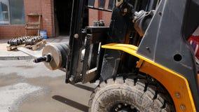 Vorkheftruckbestuurder die in beschermende vest drijfvorkheftruck bij pakhuis van vracht bedrijf door:sturen Mens op de vorkheftr stock afbeeldingen