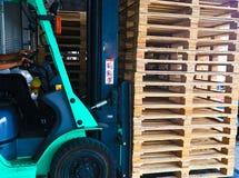 Vorkheftruckexploitant die houten pallets in pakhuislading behandelen voor vervoer aan klantenfabriek stock afbeelding
