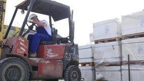 Vorkheftruckvrachtwagenchauffeur in Fabriek of Pakhuis het Drijven tussen Rijen van het Opschorten met Stapels Dozen en Verpakkin stock videobeelden