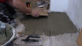 Vorlagenarbeitskraftmann legen keramische Bodenfliesen in der Küche stock video