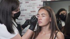 Vorlagenbrauenspezialist verteilt leicht die Farbe auf den Augenbrauen des Kunden stock video