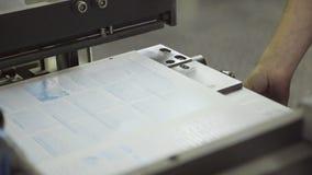 Vorlagenbuchbinder setzt Blatt der Zeitung auf Ausrüstung für Presse stock video footage