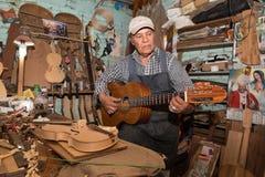 Vorlagengitarrenhersteller, der den Ton seiner Gitarre prüft Stockfotografie