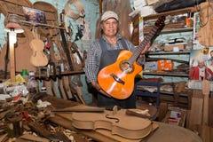 Vorlagengitarrenhersteller, der stolz sein handgemachtes Instrument zeigt Stockfotos