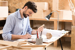 Vorlagenherstellungsberechnungen des netten jugendlichen Bauholzes von Skizzen am Arbeitsplatz Lizenzfreies Stockbild