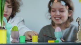 Vorlagenklasse auf der Herstellung von Ostern-Dekor Jungen- und Mädchenkampf mit Quasten, kindischer Streich-, Grüner und Gelberf stock video footage