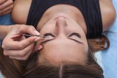 Vorlagenmake-up korrigiert und gibt Form, um mit der Zange auszuziehen, die vorher mit Hennastrauchaugenbrauen in einem Schönheit stockbild