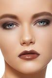 Vorm samenstelling met bruine oogschaduw en lippenstift Stock Foto's