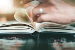 Vorm van een hart op een boek bij koffiekoffie stock fotografie