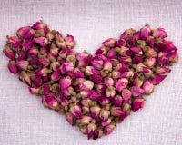 Vorm van een hart uit droge roze rozen op stof wordt gemaakt die stock foto