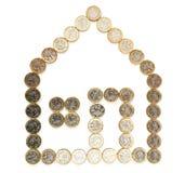 Vorm van een huis van gouden muntstukken wordt gemaakt dat stock foto