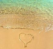 Vorm van hart op het zandstrand met kristal transparante golven Royalty-vrije Stock Afbeelding