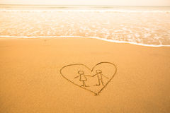 Vorm van het paar binnen hart van het overzees op het strand Stock Afbeeldingen