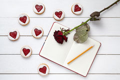 Vormde het zandkoek eigengemaakte hart koekjes met leeg notitieboekje, potlood en nam bloem op witte houten achtergrond voor toe Stock Fotografie