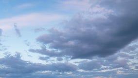 Vorming en snelle beweging van witte wolken van verschillende vormen in de blauwe hemel in de recente lente bij zonsondergang stock video