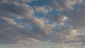 Vorming en snelle beweging van witte wolken van verschillende vormen in de blauwe hemel in de recente lente bij zonsondergang stock videobeelden