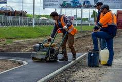 Vorming van een asfaltlaag op de stoep die een trillende machine met behulp van royalty-vrije stock foto
