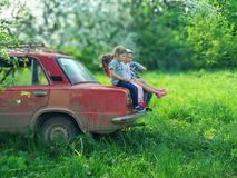 Voroblevychi village, Drohobych, Ukraine - May 29, 2018: Children sits on trunk of old car, the natural environment. Concept - Happy and carefree childhood Stock Photos