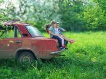 Voroblevychi wioska, Drohobych Ukraina, Maj, - 29, 2018: Dzieci siedzą na bagażniku stary samochód naturalny środowisko Zdjęcia Stock