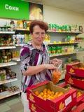 Voronež, Russia - 20 giugno 2013, la donna matura sceglie la frutta in supermercato Immagini Stock