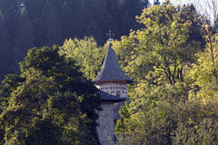Voronet monastery, Romania. Voronet monastery tower is visible through the trees in an autumn day. Voronet is a monastery from Romania, located in the town of Royalty Free Stock Image