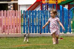 Voronezh, Rússia: 17 de junho de 2013 Uma menina com um cão que corre sob a água em um parque em um dia ensolarado quente fotos de stock royalty free