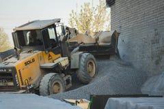 Voronezh region, Ryssland, april, 25 2019 Traktorp?fyllningar krossade stenen i produktionen av betong Gul traktorladdarspring arkivbild