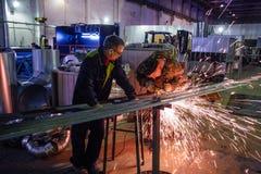 Voronezh, Rosja Około 2017: Metali pracownicy ciie metal części używać elektrycznego kółkowego ostrzarza w metalwork fabryce Zdjęcie Royalty Free