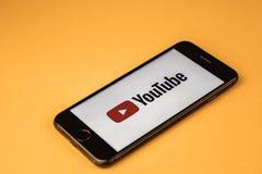 voronezh Rusia - pueden 03, 2019: Apple iPhone 7 a estrenar con el logotipo YouTube, en un fondo anaranjado YouTube es el popular fotografía de archivo libre de regalías