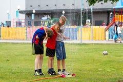 Voronezh, Rusland: 17 juni, 2013 Jongens onder de waterstralen in het park op een hete zonnige dag Vreugde, pret stock foto