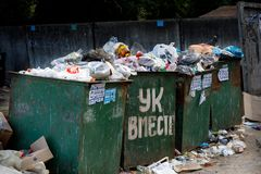 Voronezh, Russia - June 18, 2019. Garbage cans overflowing with debris and waste. Untimely removal. Large inscription in stock photo